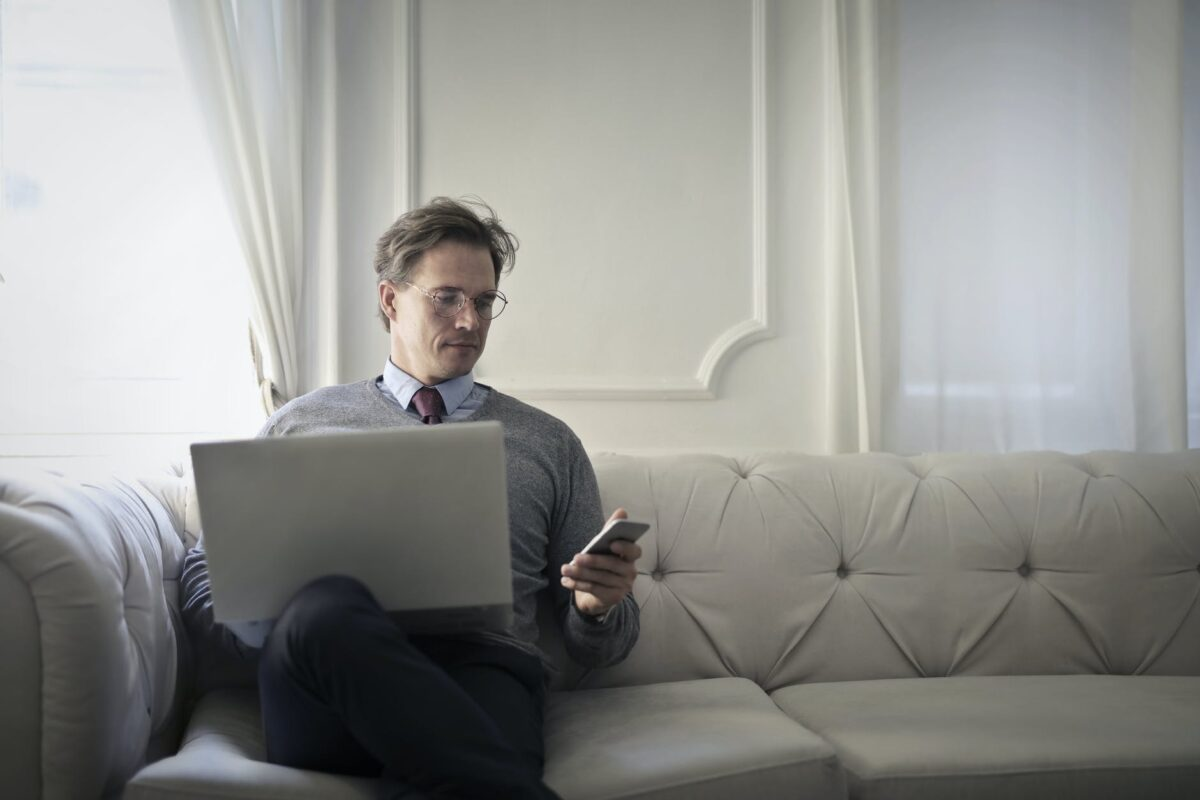 Man on a couch with a laptop and iPhone