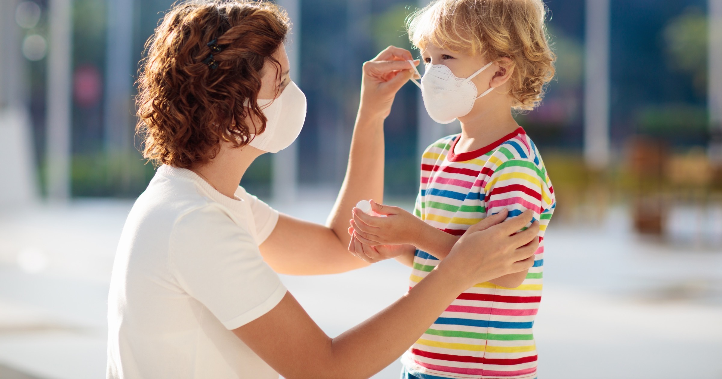 Mother putting a face mask on her child.