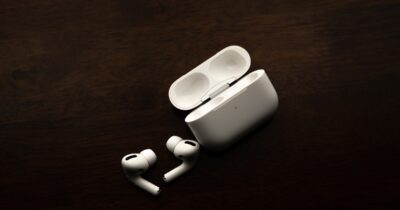 AirPods Pro against a dark brown background.