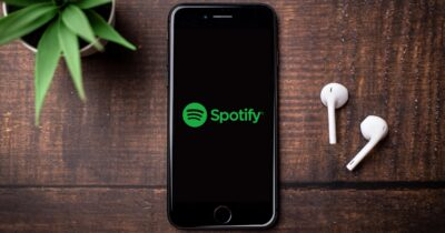iPhone on a table with airpods and the Spotify logo.